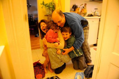 Photo: A family has a group hug in their home.