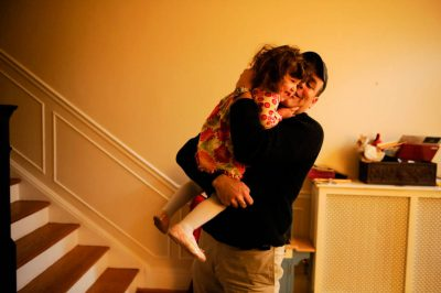 Photo: A father holds his young daugther in their home.
