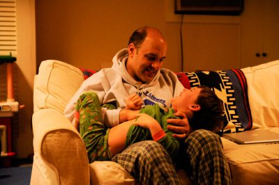 Photo: A father tickles his son in the basement of their home.