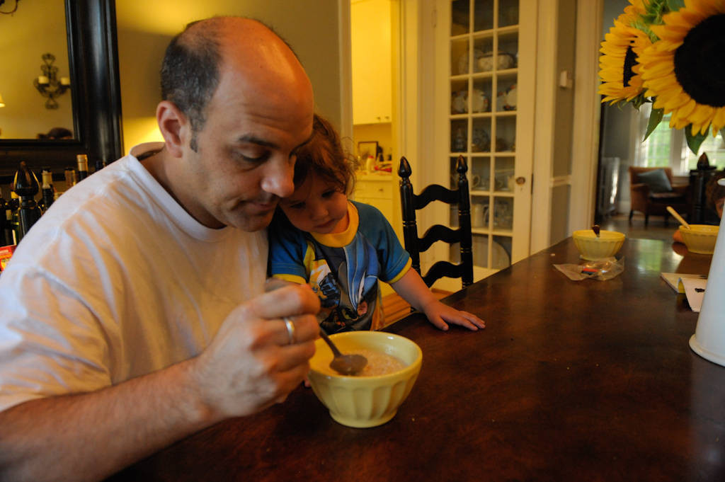 Photo: A father eats breakfast with his daughter sitting on his lap at their home in Washington D.C.