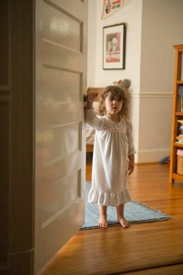 Photo: A young girl standing with her night gown on in a doorway at her home in Washington D.C.