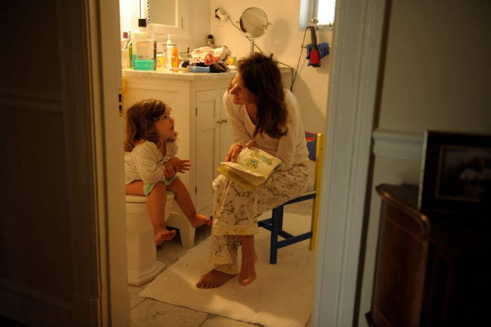 Photo: A mother sits patiently reading a book as she potty trains her daughter at their home in Washington D.C.