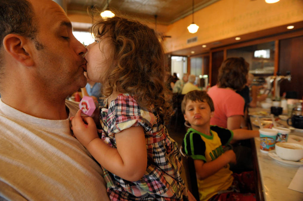 Photo: A father kisses his daughter, with his son making faces while eating at a restaurant.