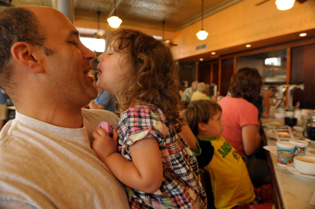 Photo: A father kisses his two year-old daughter while eating at a restaurant.