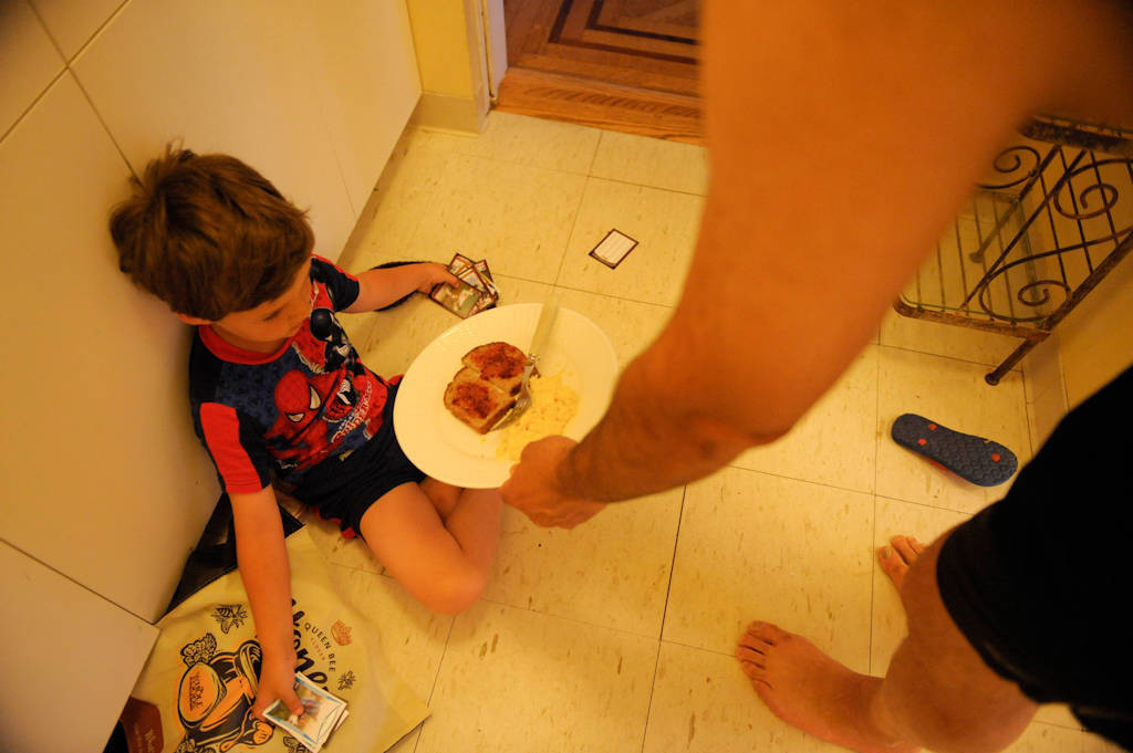 Photo: A boy sits on the floor looking at baseball cards while his father hands him breakfast at his house in Washington D.C.