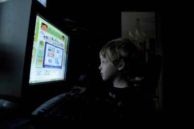 Photo: A young boy uses the computer at his home in Lincoln, NE.