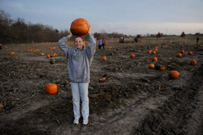 Photo: An adolescent girl holds a pumpkin at Roca Berry farm in Roca, NE.
