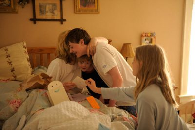 Photo: A woman is embraced by her children as she opens her Mother's Day presents.