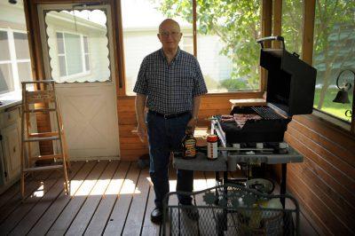 Photo: A senior man cooks hamburgers.
