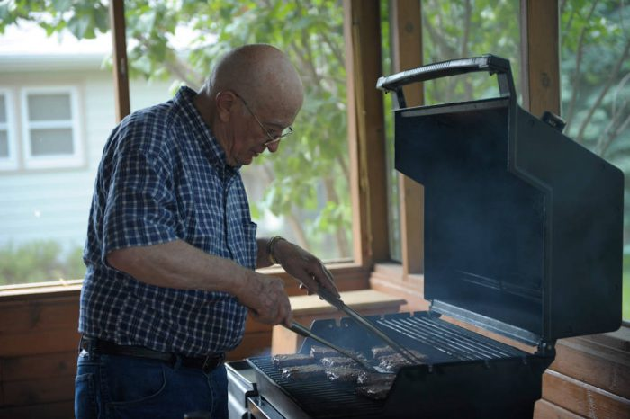 Photo: A senior man cooks hamburgers.