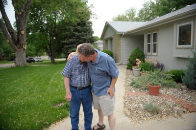 Photo: A senior man and his son embrace outside a home in Elkhorn, Nebraska.