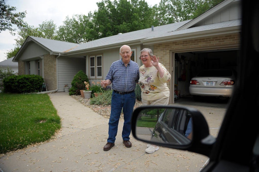 Photo: A senior man and woman wave goodbye from their home in Nebraska.