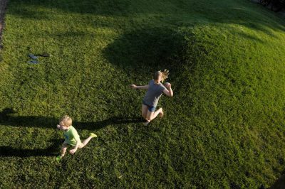 Photo: A brother and sister play in grass.