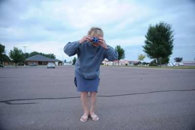 Photo: A woman takes a photograph in Redwood Falls, MN.