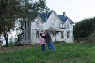 Photo: Husband and wife outside farm house.