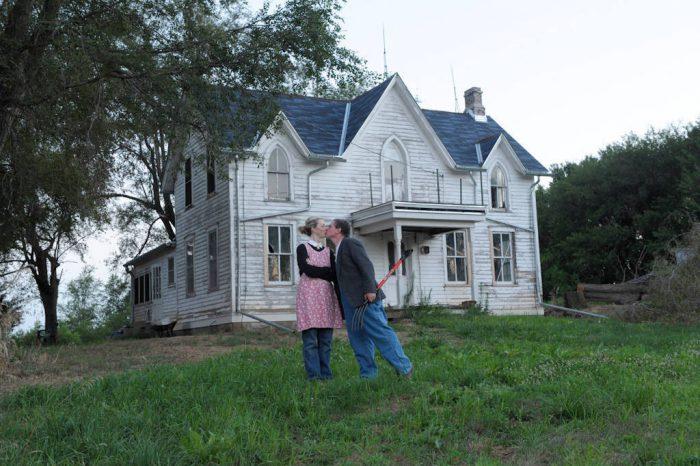 Photo: Husband and wife outside farm house.