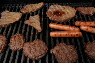Photo: Steaks, hot dogs and hamburgers sear on a grill.