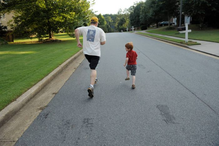 Photo: A father and his five year-old son walk in their neighborhood.