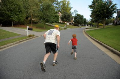 Photo: A father and his five year-old son run through their neighborhood.