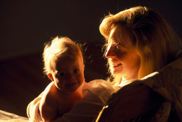 Photo: A mother holding her baby daughter in warm golden light.