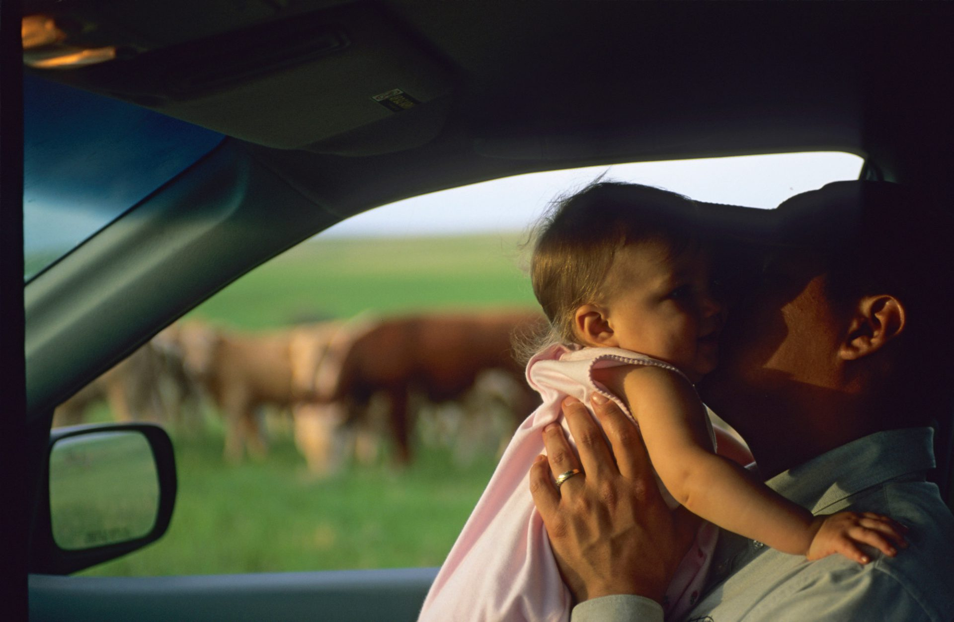 Photo: A rancher kisses his baby daughter inside a vehicle.
