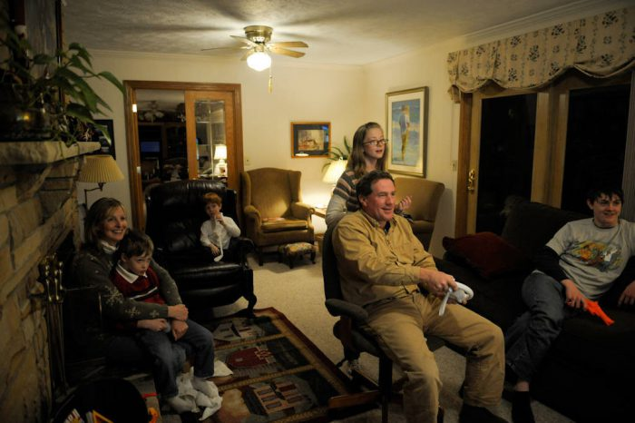 Photo: A family plays video games together.