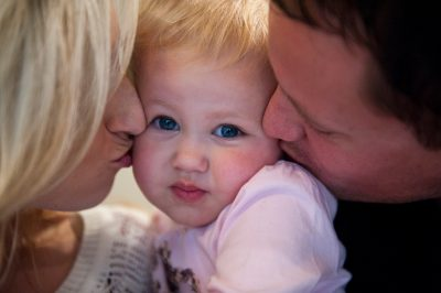 Photo: A young couple kiss the cheeks of their little girl in Lincoln, Nebraska.
