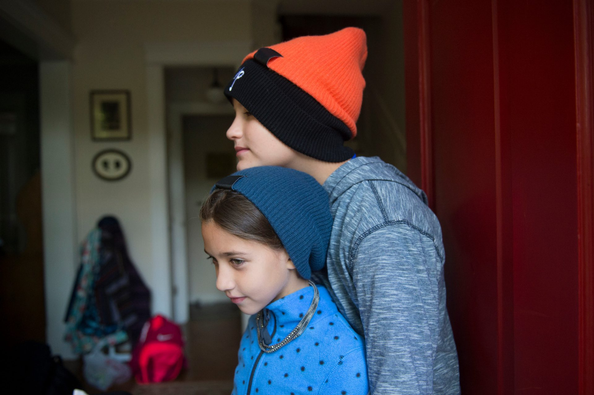 Photo: A brother leans on his sister in their home.
