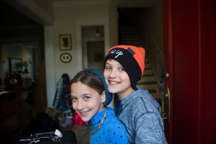 Photo: A brother and sister smile in their home.