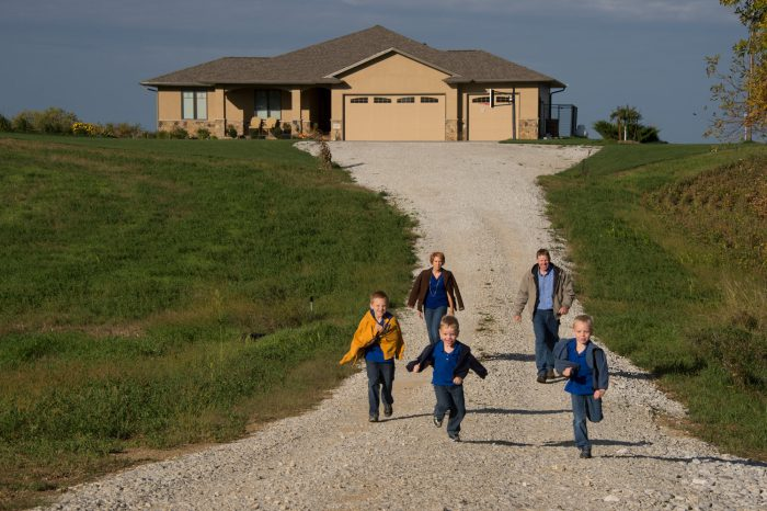 Photo: A family of five walk down the gravel road in front of their house.