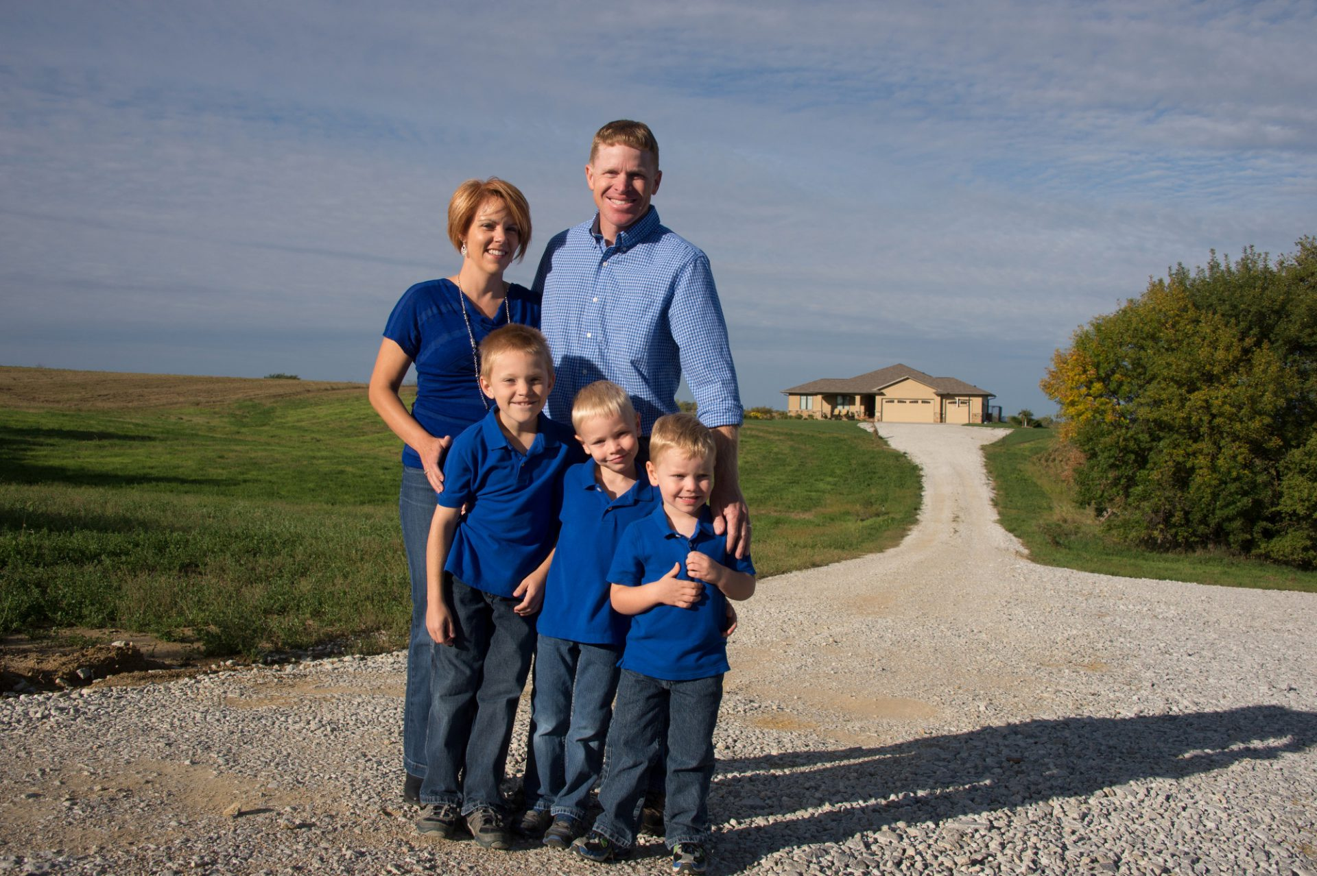 Photo: A family of five stand on the gravel road in front of their house.