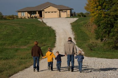 Photo: A family of five walk up the gravel road in front of their house.
