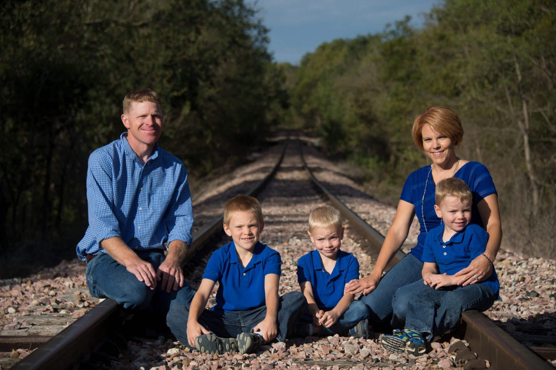 Photo: A family of five pose for a portrait on railroad tracks.