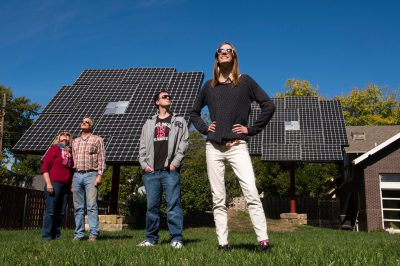 Photo: A family of four stands in front of solar panels in their backyard.