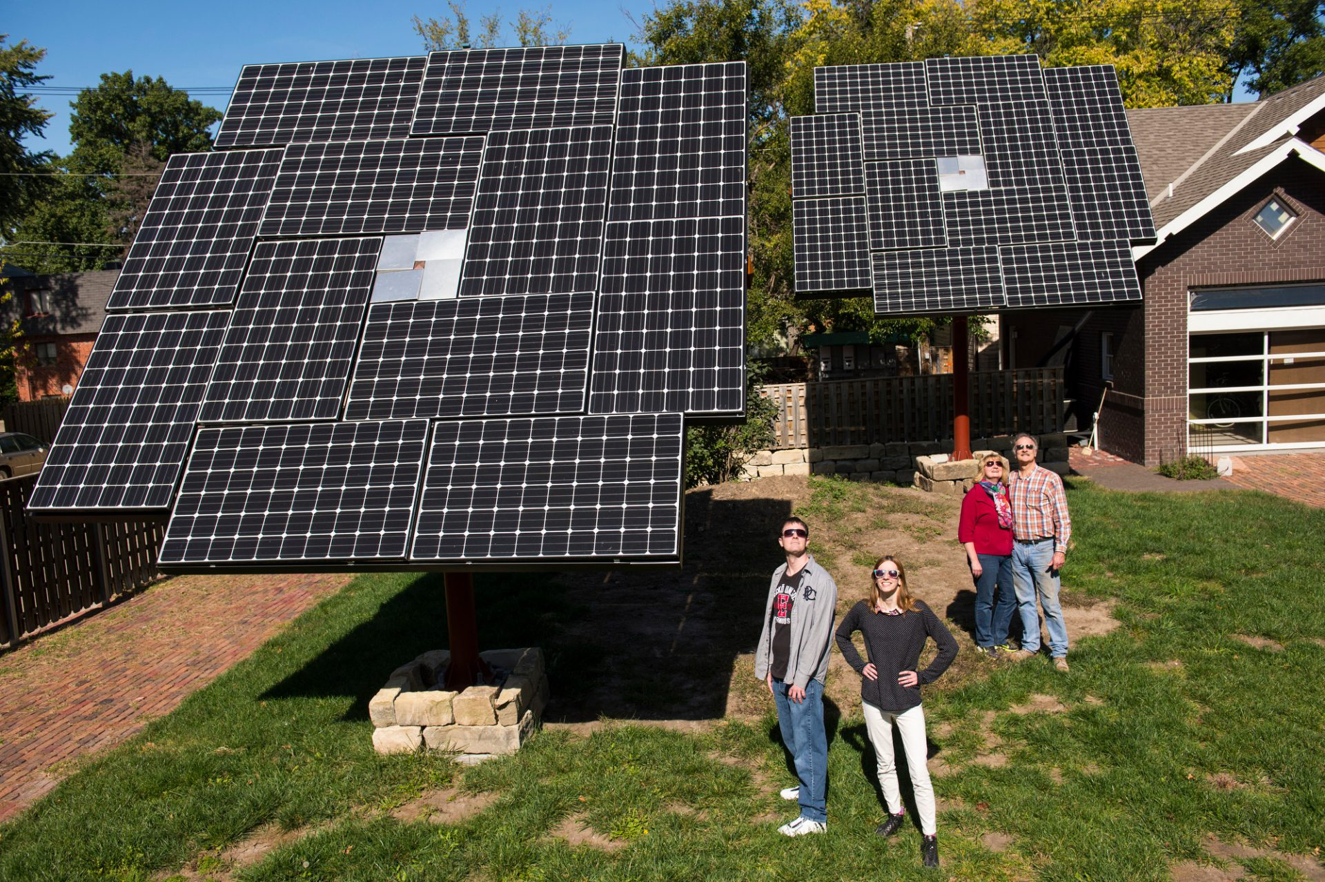 Photo: A family of four stands in their backyard with their new solar panels.