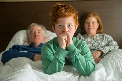 Photo: Portrait of an elementary age boy with his parents.
