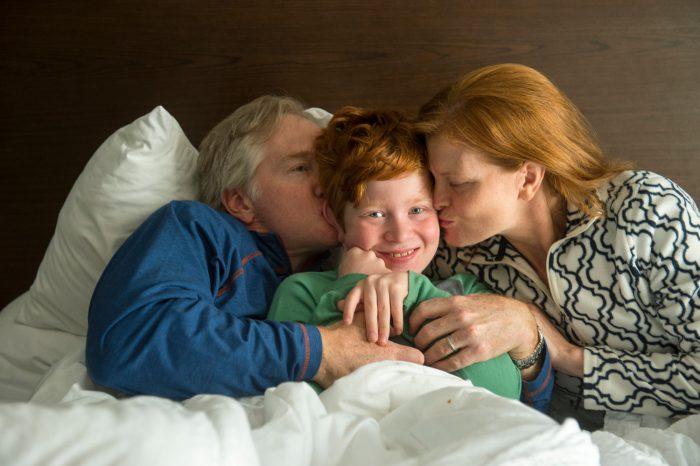 Photo: An elementary age boy receives kisses on the cheek from his parents.