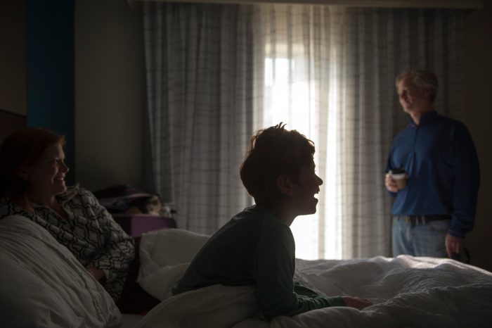 Photo: A family of three in a hotel room.