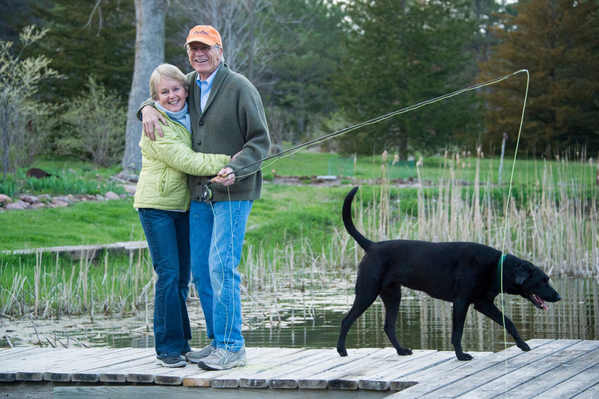 Photo: A couple with their dog at their fishing pond.