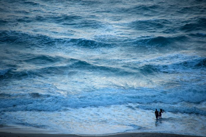 Photo: A couple plays in the ocean waves at dusk at Riviera Beach.