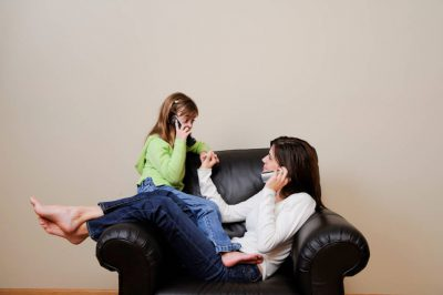 Photo: A woman and her young daughter use a telephone in their living room.