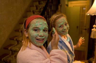 Photo: Two young girls put on mud masks during a sleepover.