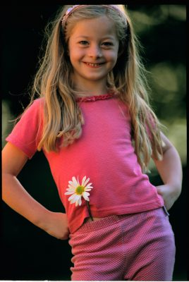 Photo: Portrait of a young girl with a daisy.