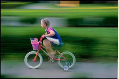 Photo: A girl speeds by on her bicycle with training wheels.