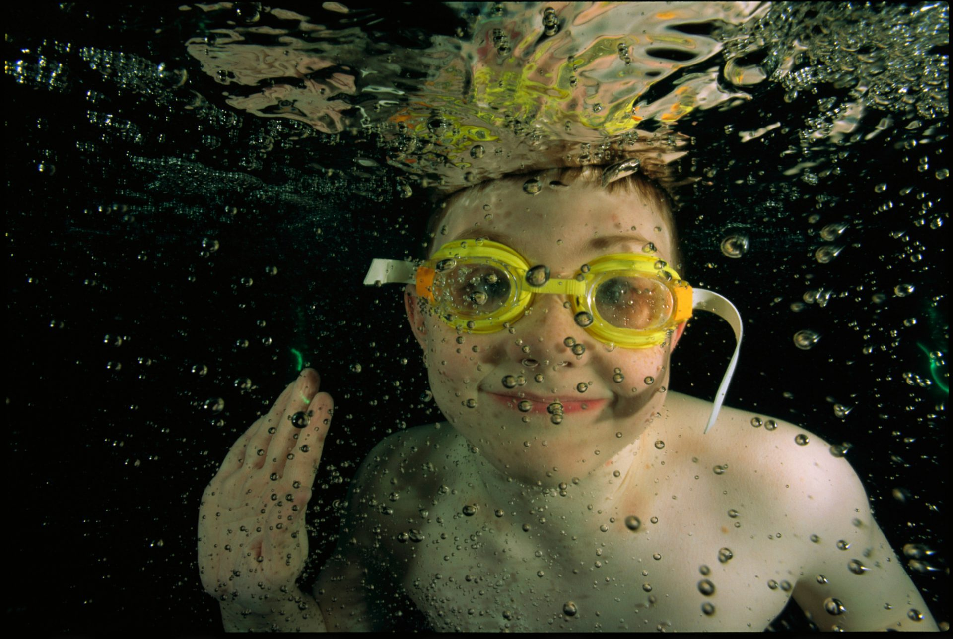 Photo: A boy grins at the camera while swimming underwater.