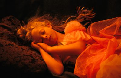 Photo: A girl wearing a princess dress, asleep on a sofa.