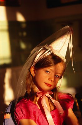 Photo: A young girl plays dress-up, wearing a fancy hat.