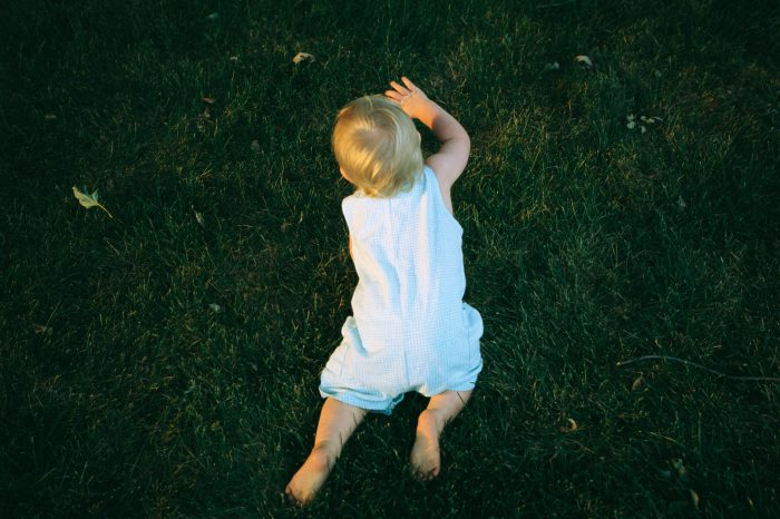 Photo: A bird's-eye view of a baby boy crawling on grass.
