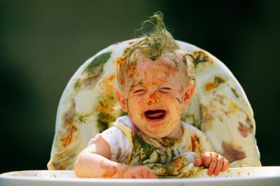 Photo: A baby boy, covered in food, cries in his high chair.