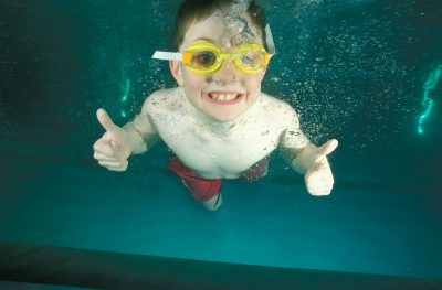 Photo: A boy smiles for the camera while swimming.